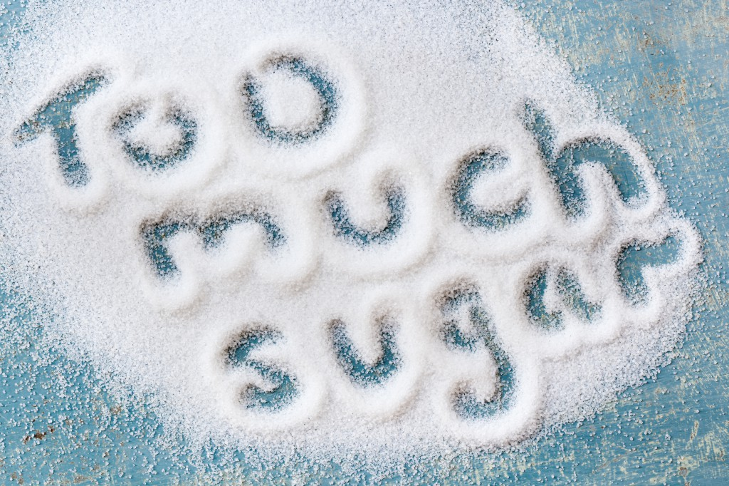 "The words ""too much sugar"" written in sugar grains.  Overhead vi"